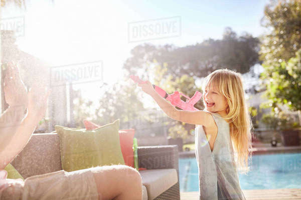 Playful daughter with squirt gun spraying father on sunny summer patio Royalty-free stock photo