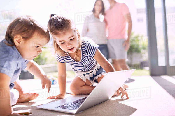 Brother and sister using laptop on sunny floor Royalty-free stock photo