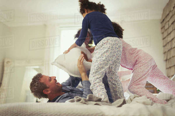 Playful multi-ethic father and daughters pillow fighting on bed Royalty-free stock photo