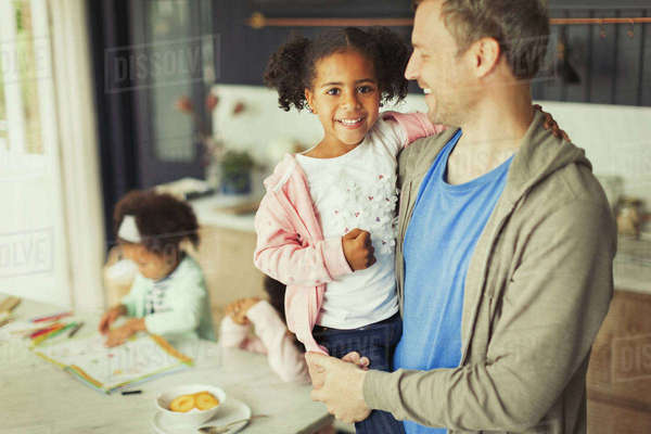 Portrait smiling multi-ethnic father and daughter in kitchen Royalty-free stock photo