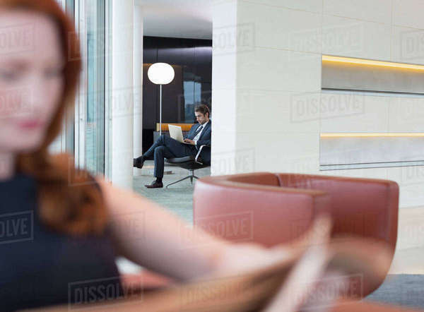 Business people using laptop and reading newspaper in lounge Royalty-free stock photo