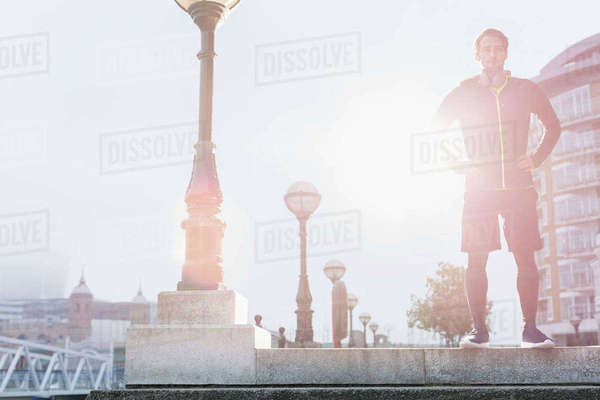 Portrait confident male runner standing at sunny urban lamppost Royalty-free stock photo