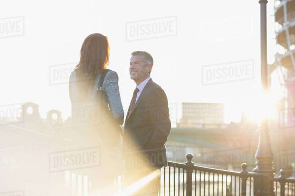 Businessman and businesswoman talking at sunny urban railing Royalty-free stock photo
