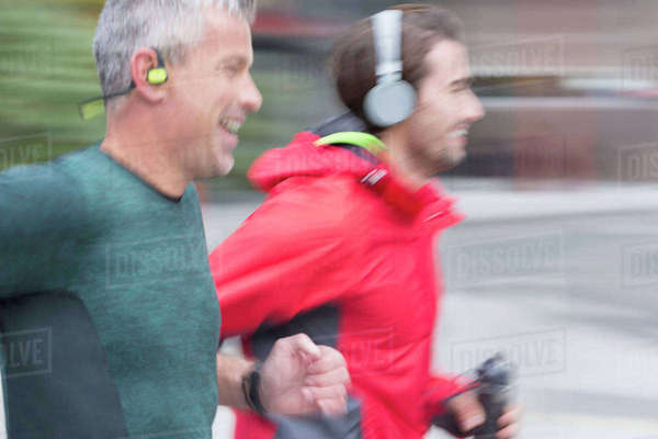 Smiling male runners with headphones running Royalty-free stock photo