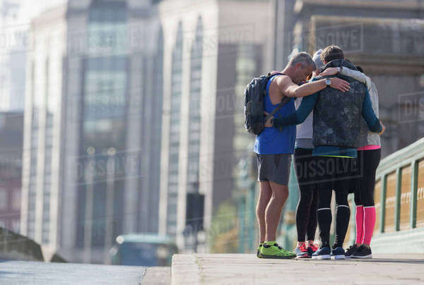 Runners connected in a huddle on sunny urban sidewalk Royalty-free stock photo
