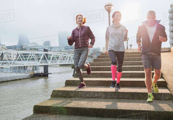 Runners running down steps along sunny urban waterfront Royalty-free stock photo