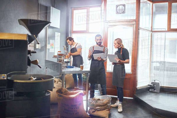 Coffee roasters with clipboard and digital tablet meeting Royalty-free stock photo