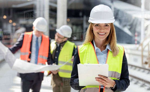Portrait smiling female engineer with clipboard at construction site Royalty-free stock photo