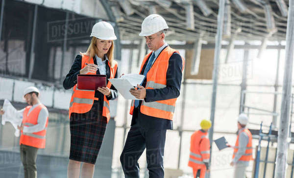 Engineers with clipboards meeting at construction site Royalty-free stock photo