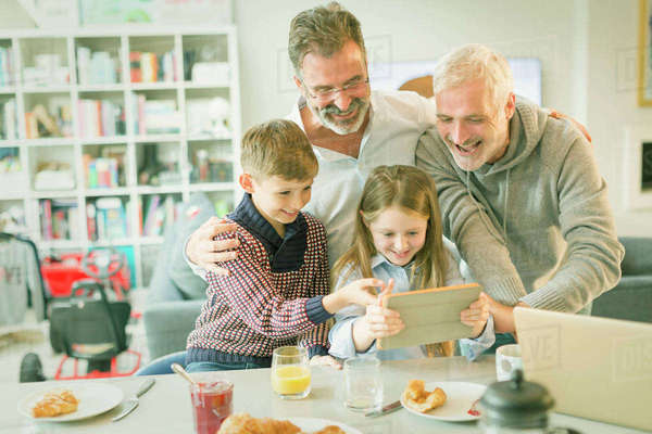 Male gay parents and children video messaging with digital tablet in morning kitchen Royalty-free stock photo