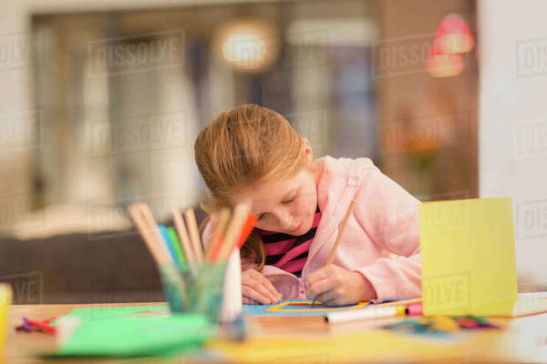 Focused girl drawing, doing crafts at table Royalty-free stock photo