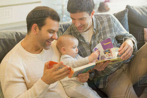 Male gay parents reading book to baby son on sofa Royalty-free stock photo