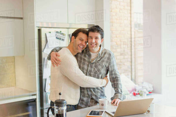 Portrait affectionate male gay couple hugging at laptop in kitchen Royalty-free stock photo