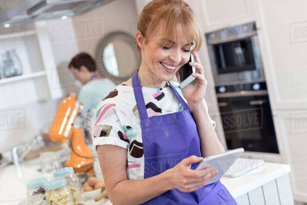 Smiling caterer working, talking on cell phone and using digital tablet in kitchen Royalty-free stock photo