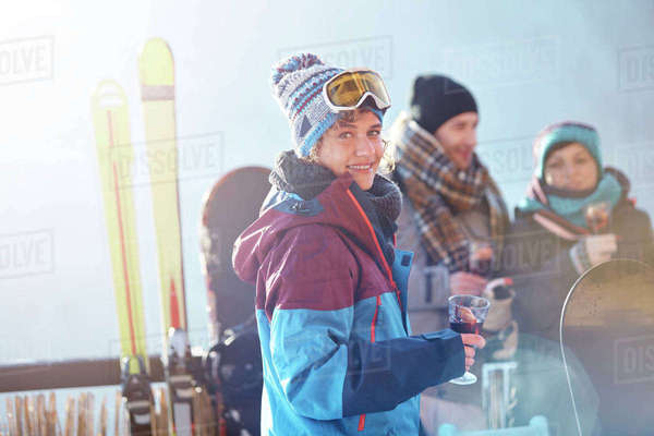 Portrait smiling female skier drinking cocktail on balcony with friends apres-ski Royalty-free stock photo