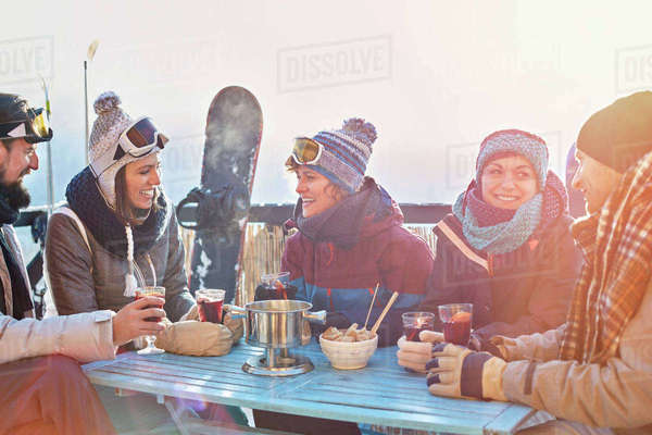 Snowboarder friends drinking cocktails on sunny balcony apres-ski Royalty-free stock photo