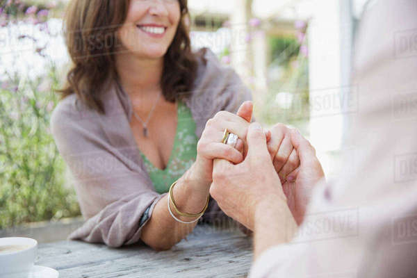 Close up affectionate mature couple holding hands at patio table Royalty-free stock photo