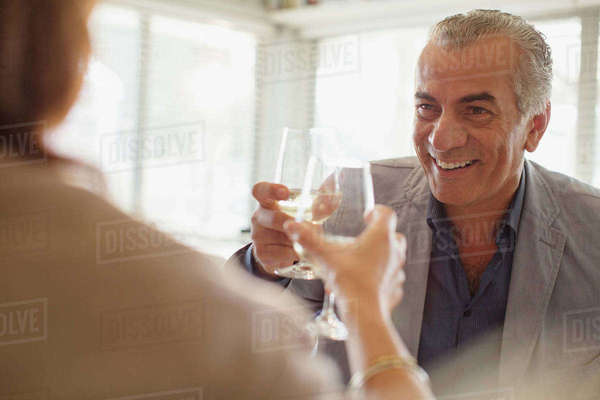 Smiling senior man drinking wine, toasting wine glasses with woman at restaurant Royalty-free stock photo