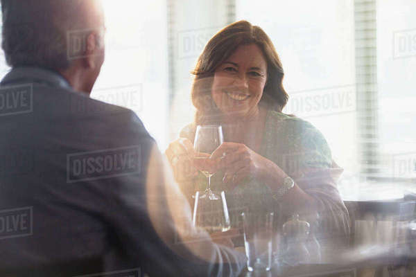 Smiling mature couple drinking wine, dining at restaurant table Royalty-free stock photo