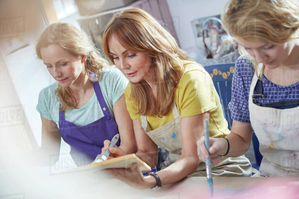 Female artists painting picture frames in art class workshop - Stock ...