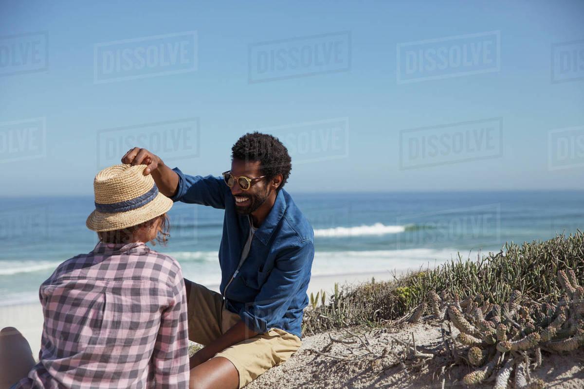 Smiling Man Placing Hat On Friend Sunny Summer Ocean Beach