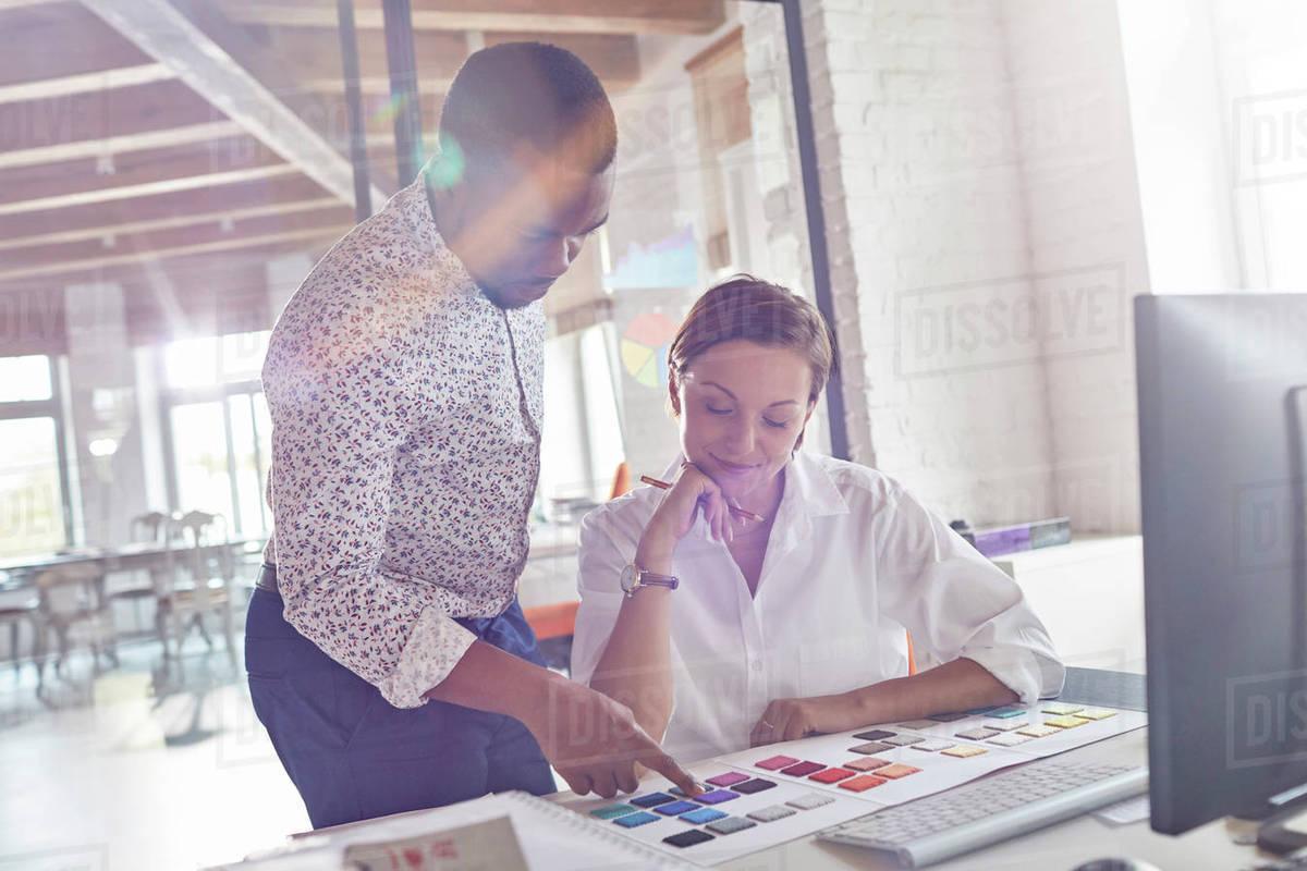 design professionals discussing color swatches in office - Interior Design Professionals