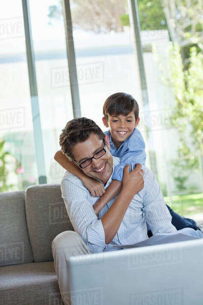 Father and son using laptop on sofa Royalty-free stock photo