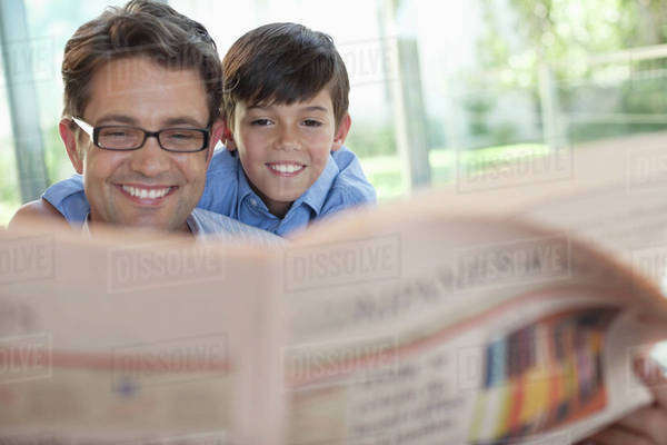 Father and son reading newspaper together Royalty-free stock photo