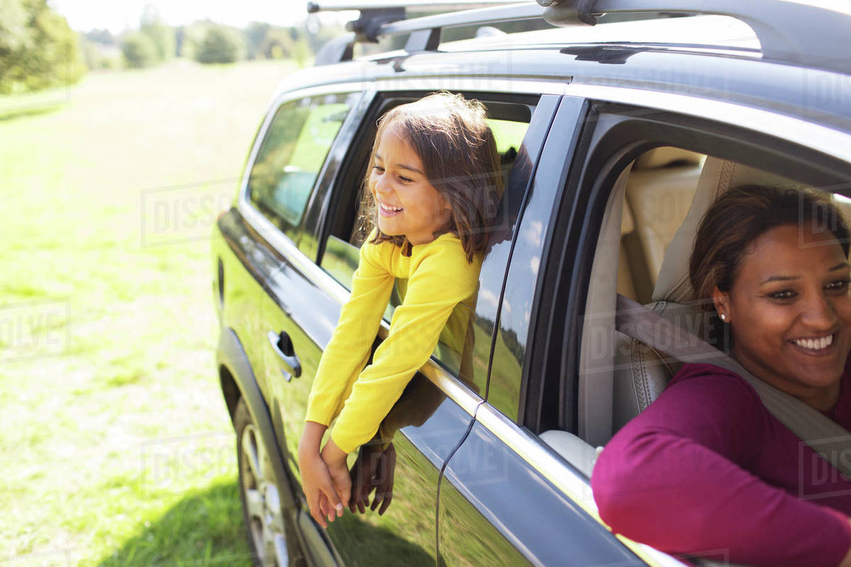 Carefree girl leaning out window of car Royalty-free stock photo