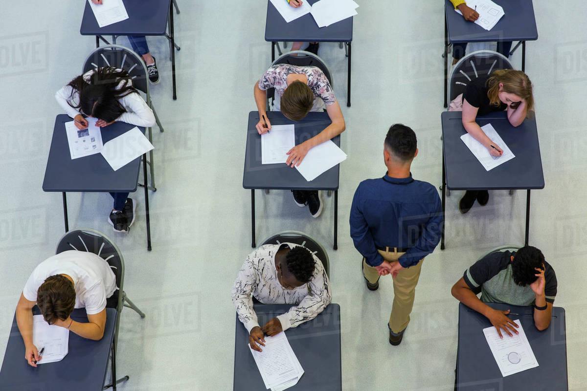 High school teacher supervising students taking exam at desks Royalty-free stock photo