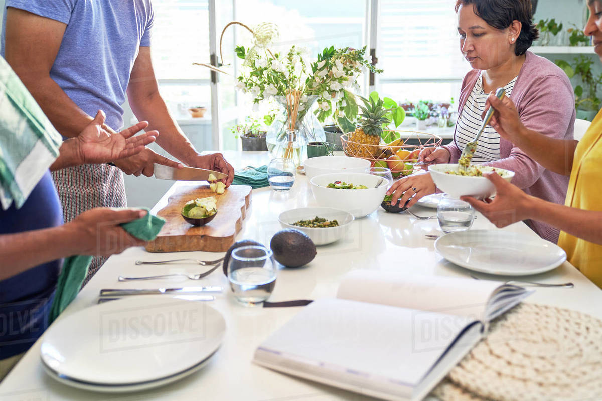Couples cooking and eating at kitchen island Royalty-free stock photo