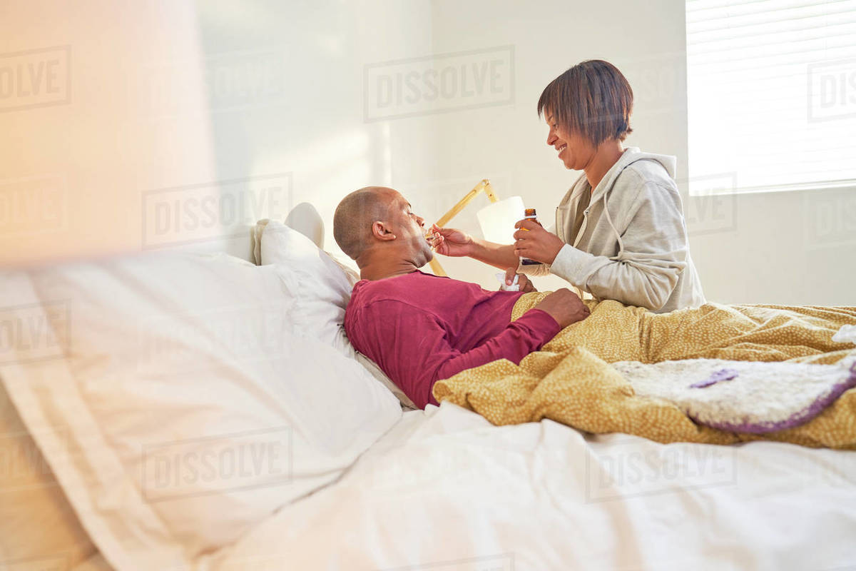 Affectionate wife giving cough syrup to sick husband in bed Royalty-free stock photo