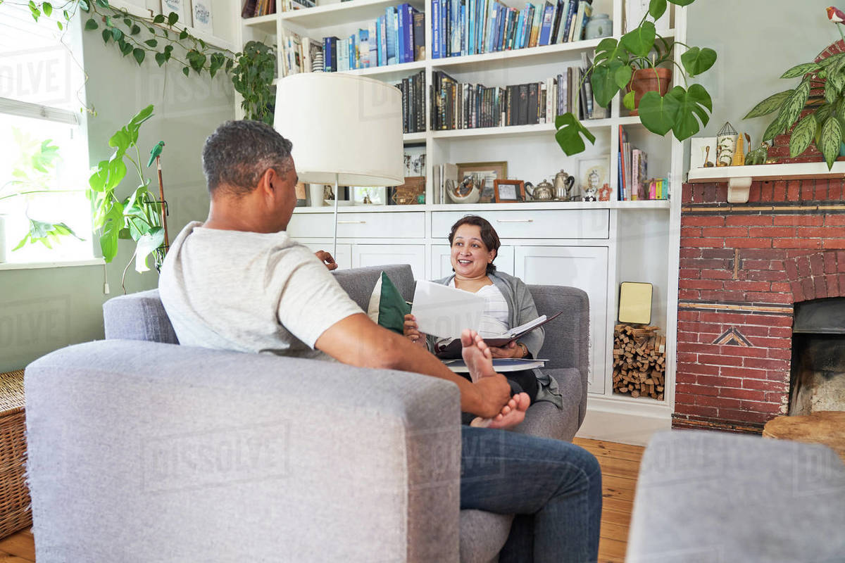 Couple talking and reading on living room sofa Royalty-free stock photo