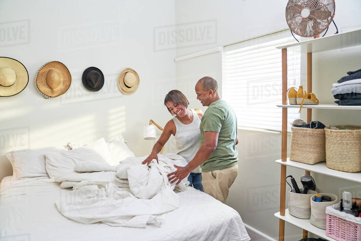 Happy couple making bed in sunny bedroom Royalty-free stock photo