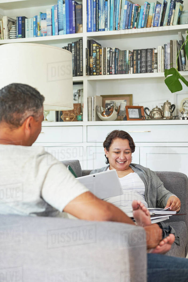 Mature couple with digital tablet on living room sofa Royalty-free stock photo