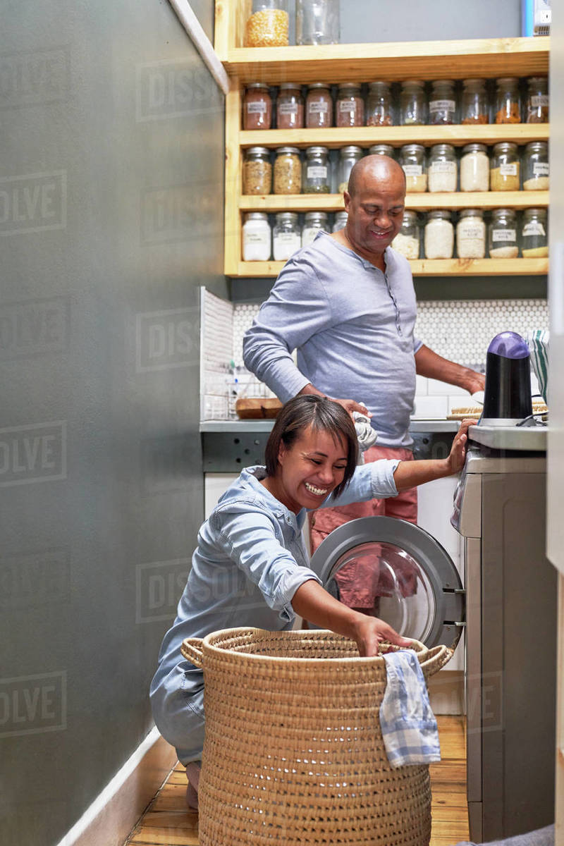 Happy couple doing laundry in kitchen Royalty-free stock photo