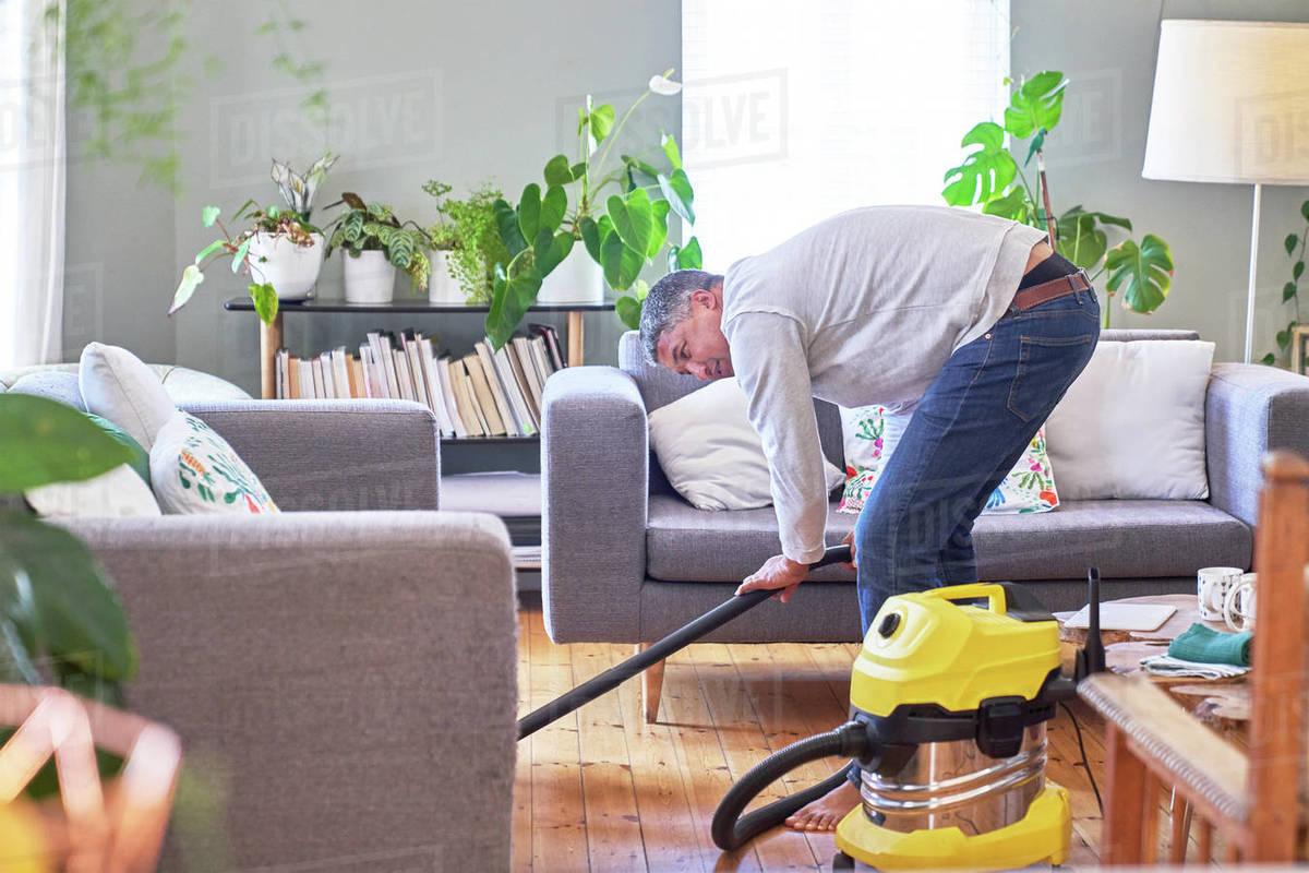Mature man vacuuming living room Royalty-free stock photo