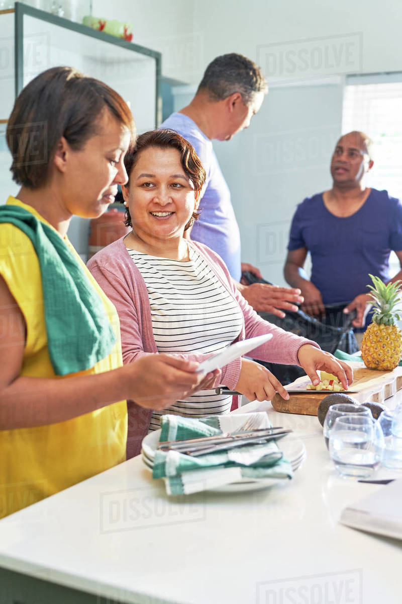 Mature couple friends talking and cooking in kitchen Royalty-free stock photo