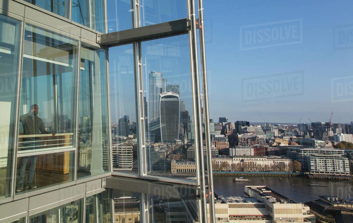 Businessman talking on smart phone at sunny modern highrise window Royalty-free stock photo