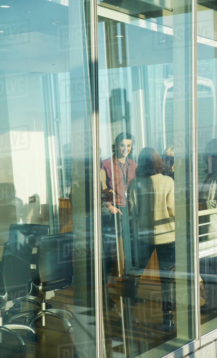 Business people talking at sunny office window Royalty-free stock photo