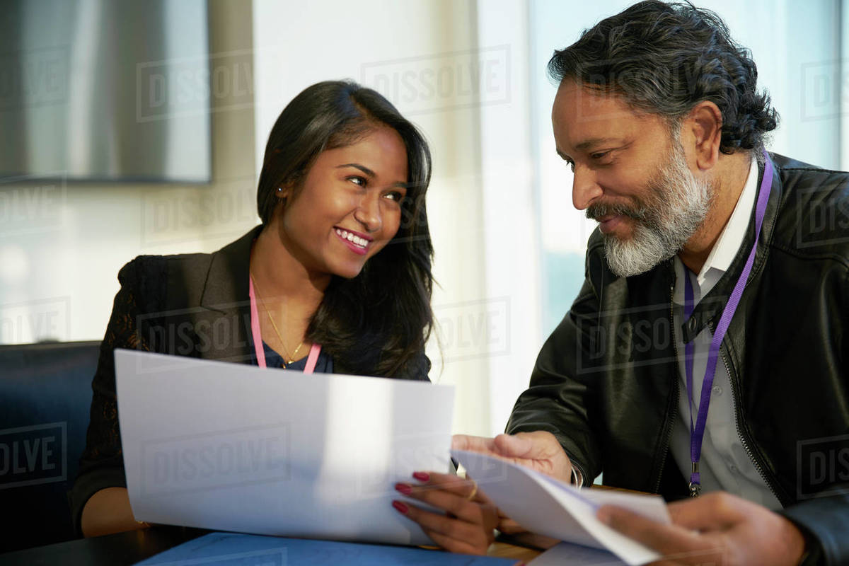 Smiling business people discussing paperwork in meeting Royalty-free stock photo