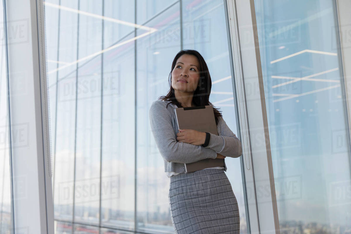Thoughtful businesswoman holding digital tablet at highrise window Royalty-free stock photo