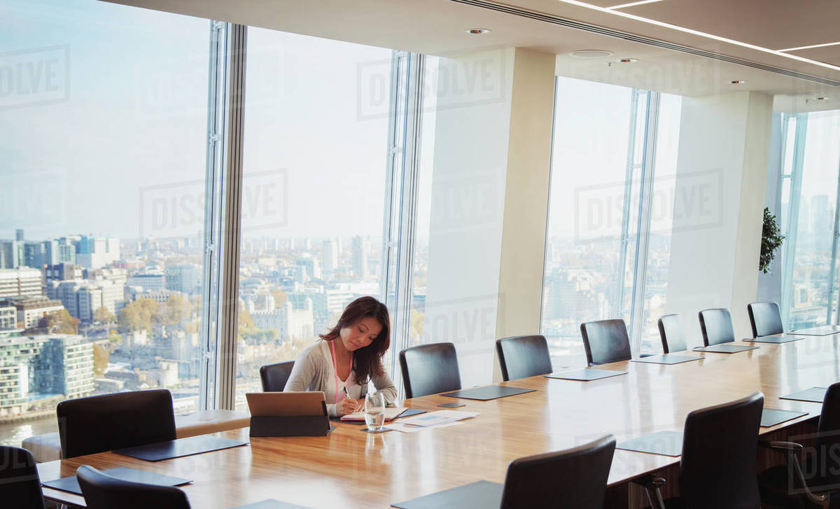 Dedicated businesswoman preparing in sunny urban conference room Royalty-free stock photo
