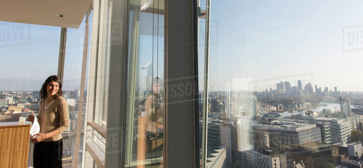 Smiling businesswoman in sunny urban highrise office window Royalty-free stock photo