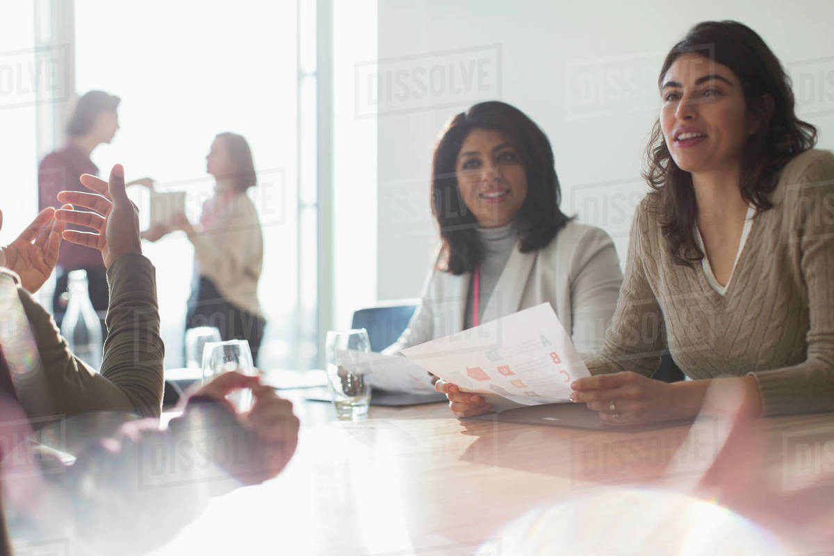 Businesswomen listening in sunny conference room meeting Royalty-free stock photo