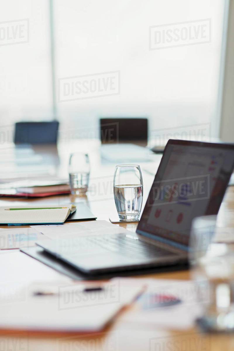 Laptop and paperwork on conference room table Royalty-free stock photo