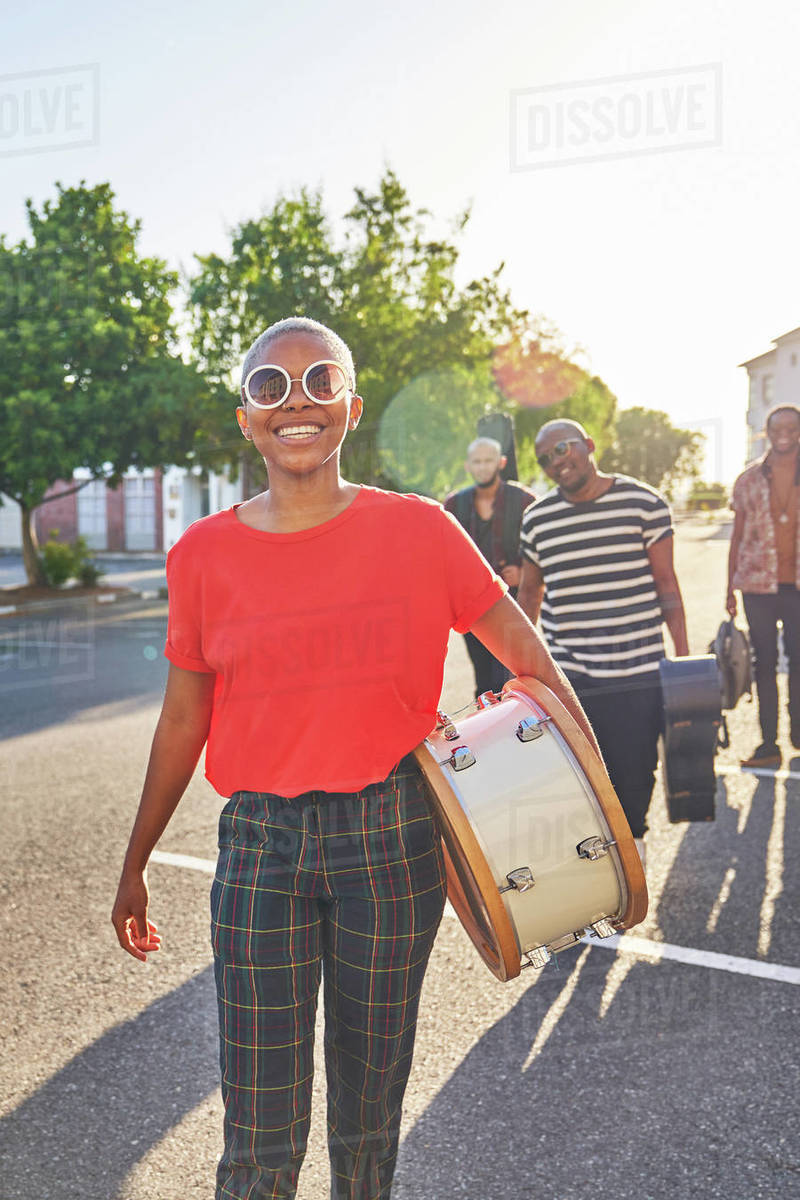 Portrait happy female musician carrying drum in sunny street Royalty-free stock photo