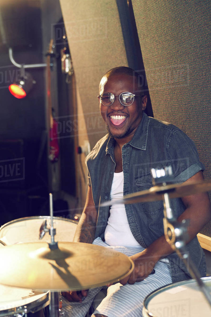 Portrait happy male drummer practicing at drums Royalty-free stock photo