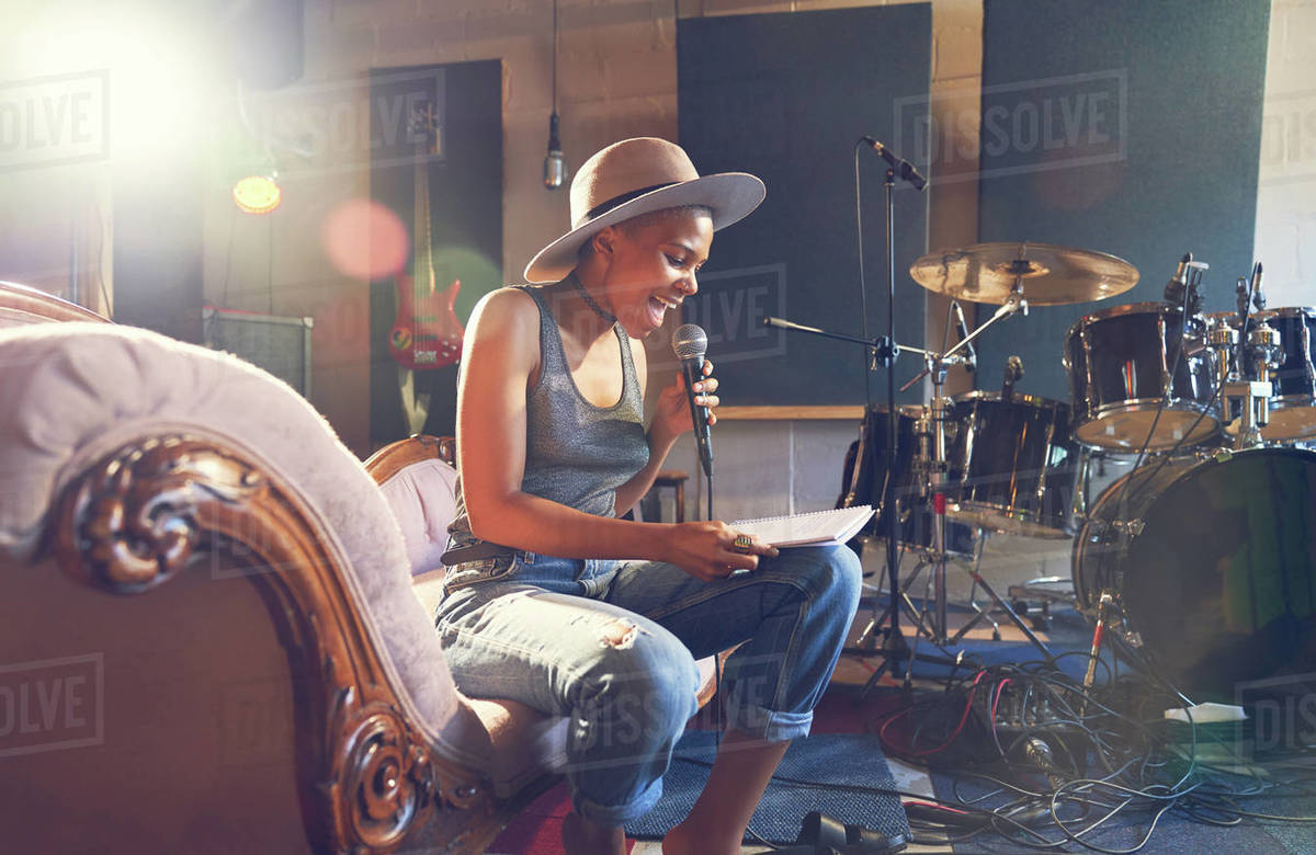 Young female musician singing and song writing in recording studio Royalty-free stock photo