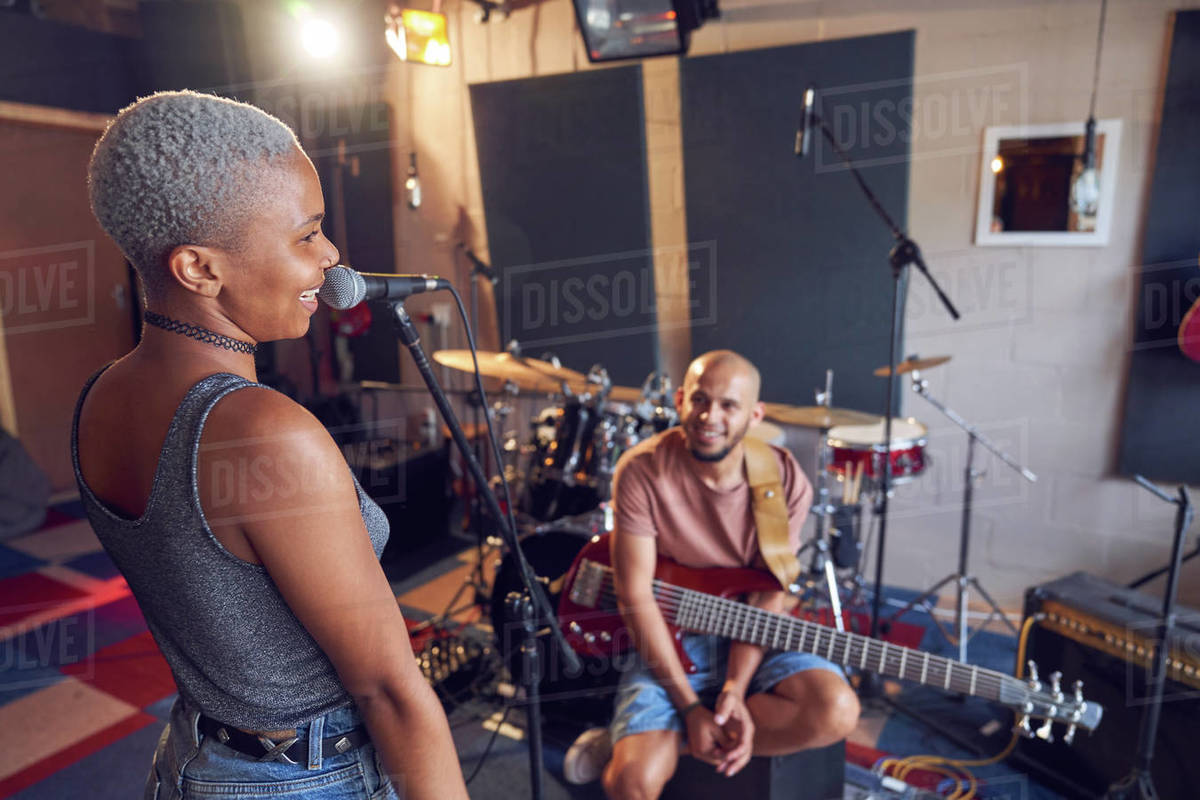 Smiling musicians practicing in recording studio Royalty-free stock photo